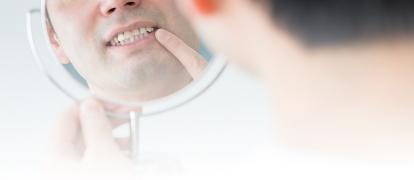 鏡で歯を見る男性